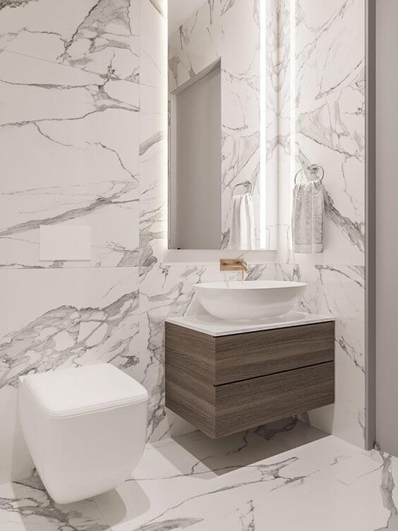 Banheiro com revestimento marmorizado cinza e móveis chiques de madeira