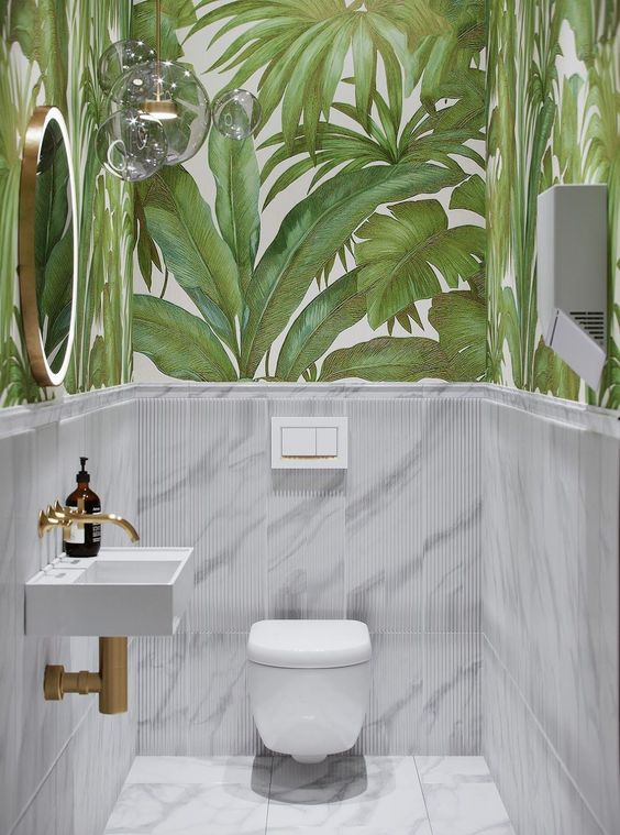 Banheiro com revestimento verde de folhas