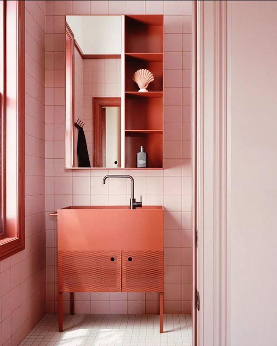 Banheiro decorado com gabinete na cor coral e revestimento rosa claro