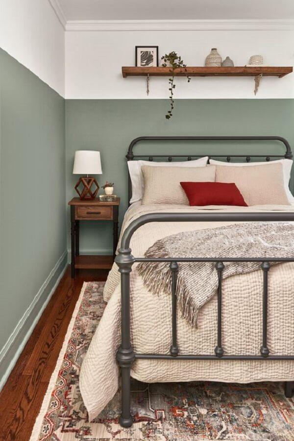 Cabeceira de ferro e mesa de cabeceira retrô de madeira decoram o quarto de casal