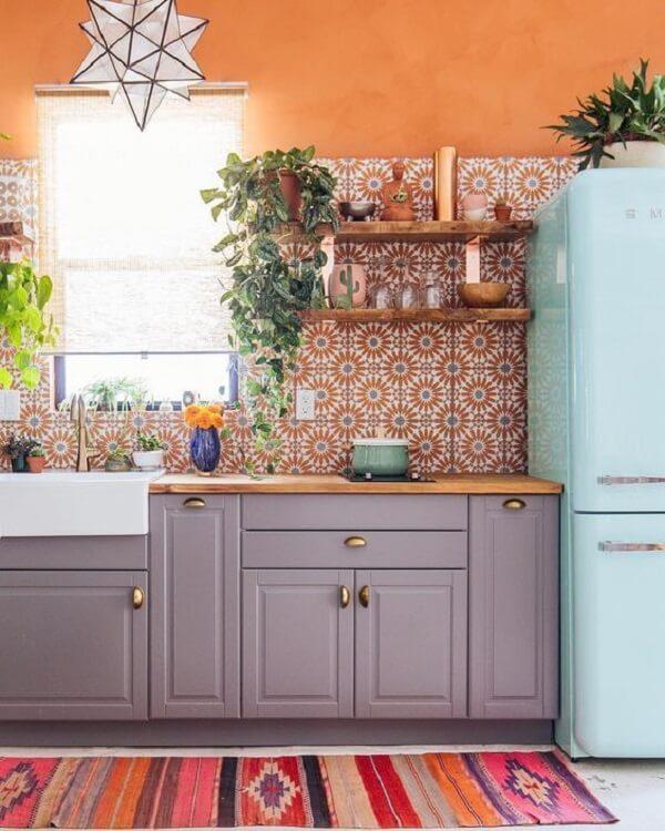 Cozinha com azulejo antigo com nuances de laranja alegram a decoração
