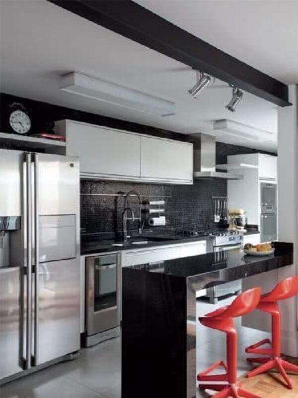 Cozinha com pastilha preta e banquetas vermelhas