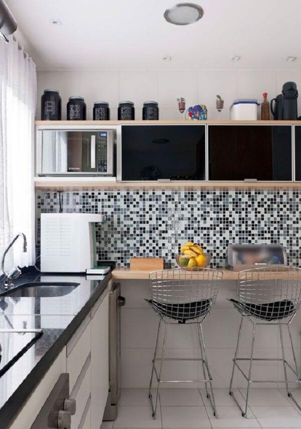 Cozinha com pastilha preta e branca, bancada de madeira e cadeiras cromadas