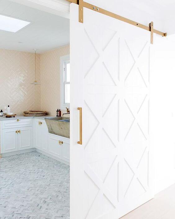 Cozinha com porta branca e detalhes dourados