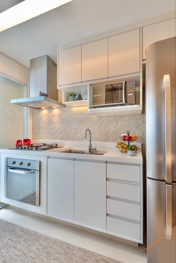 Cozinha com revestimento bege e armário branco