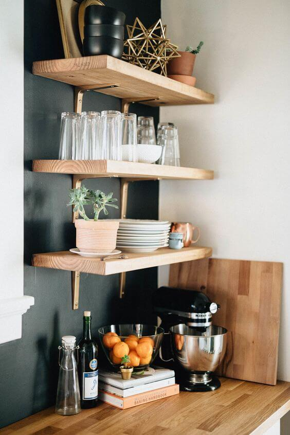 Cozinha organizada com prateleiras e mão francesa dourada