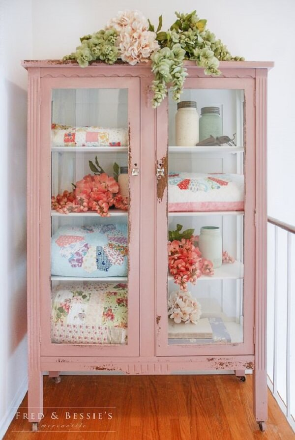 Cristaleira rústica em tom rosa com rodízios que facilitam sua movimentação