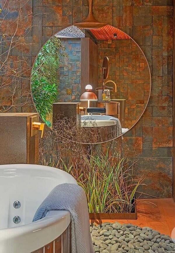 Decoração de banheiro com banheira, espelho redondo e revestimento de pedra ferro
