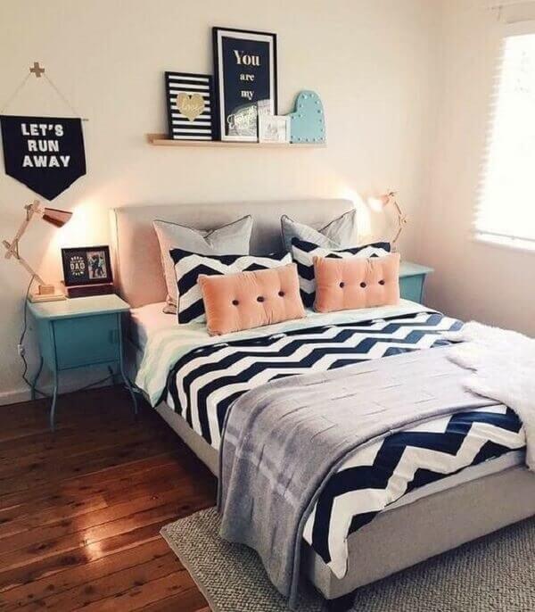 Decoração de quarto simples de casal com quadros, almofadas e mesa de cabeceira retrô azul