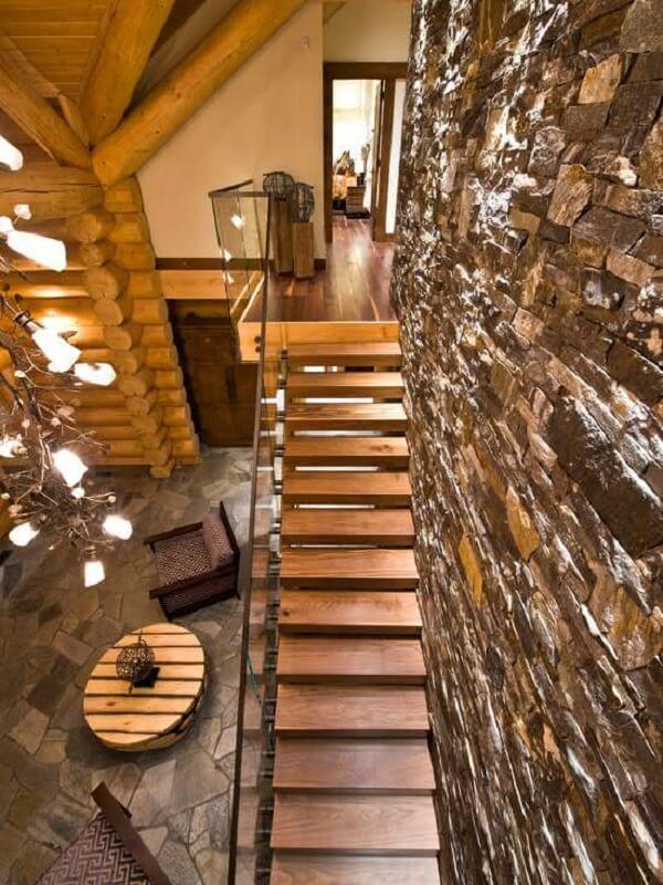 Decoração rústica com parede de pedra e revestimento para escada em madeira