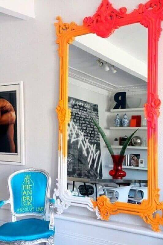 Espelho grande com moldura colorida e poltrona azul ao lado