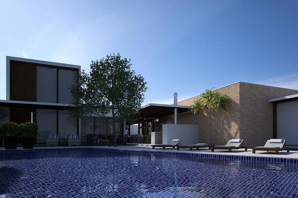 Espreguiçadeiras de madeira e azulejo azul para piscina decoram a área de lazer do terreno