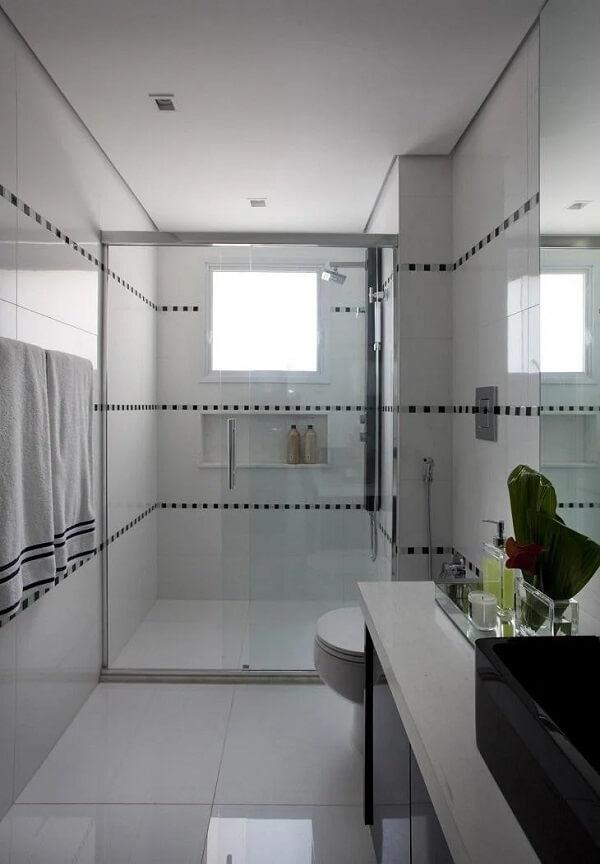 Faixas no banheiro foram criadas com revestimento pastilha preta e branca