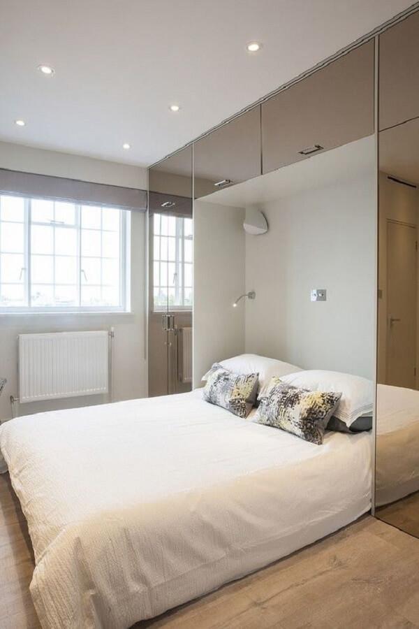 Guarda-roupa embutido com cama e acabamento espelhado