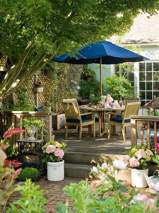 Jardim com mesa para área externa e guarda sol azul