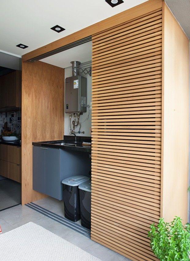 Lavanderia escondida por uma porta de correr de madeira