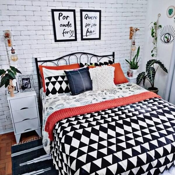 Mesa de cabeceira retrô branca com três gavetas foram posicionadas ao lado da cama de casal