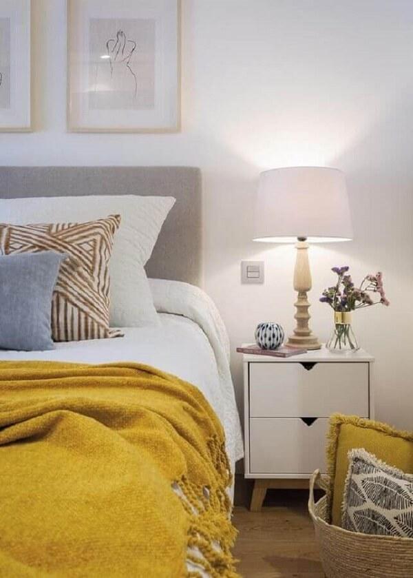 Mesa de cabeceira retrô com gavetas para decoração de quarto branco com manta amarela sobre a cama