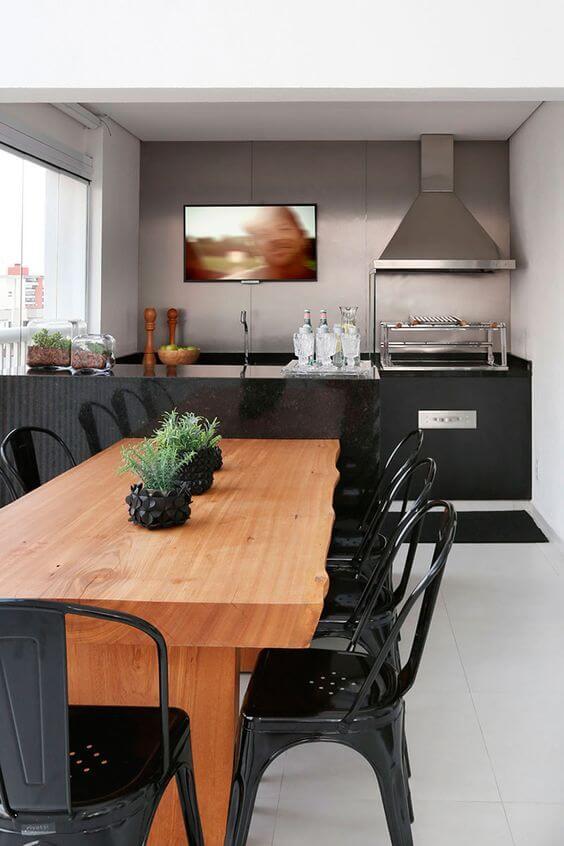 Mesa de madeira para área externa com cadeiras pretas industriais
