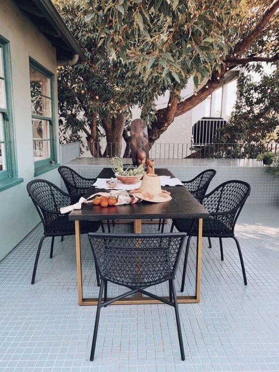 Mesa para área externa com cadeiras pretas e modernas