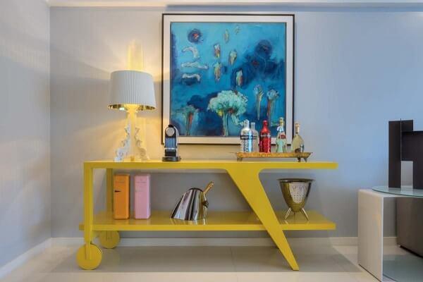 Modelo de aparador bar amarelo acomoda garrafas e um sofisticado abajur