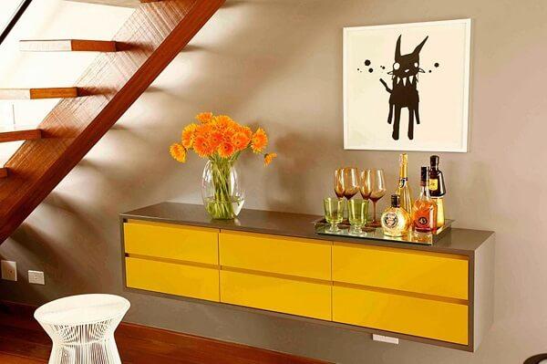 Modelo de aparador bar amarelo suspenso otimiza o espaço do cômodo