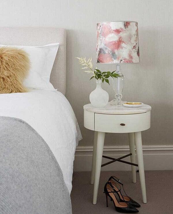 Modelo de mesa de cabeceira retrô com tampo redondo branco e pés palitos