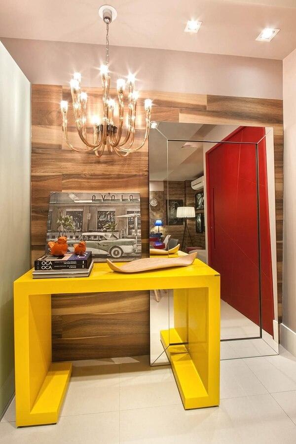 O aparador amarelo com espelho de chão decoram o hall de entrada do imóvel