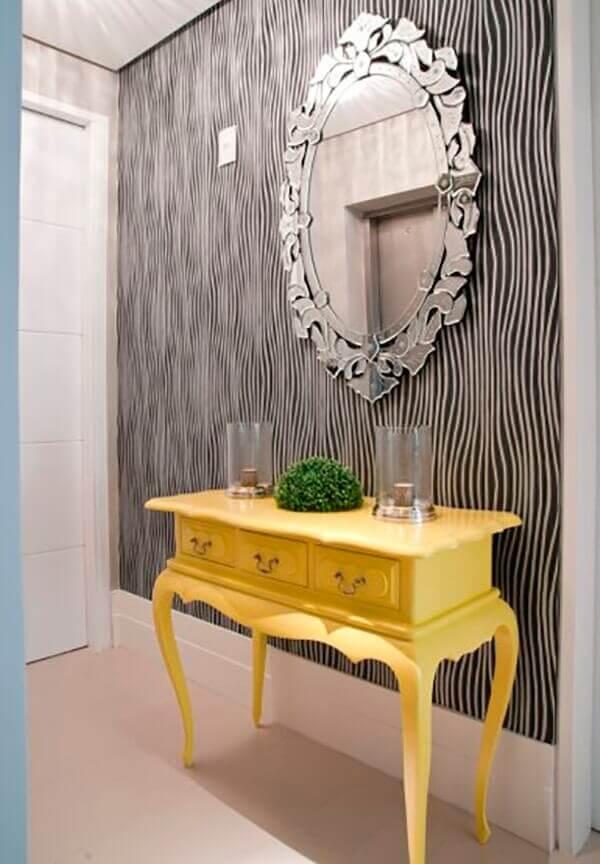 O aparador amarelo com espelho fixado na parede decora a entrada da casa