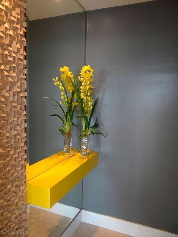 O aparador amarelo com espelho se destaca no hall de entrada da casa