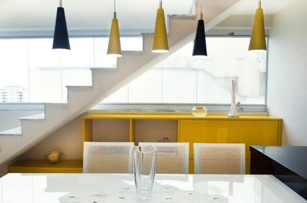 O aparador amarelo combina com as luminárias do ambiente