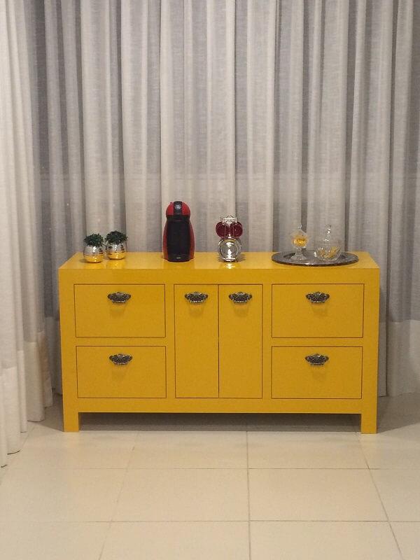 O aparador amarelo para sala serve de apoio para cafeteira