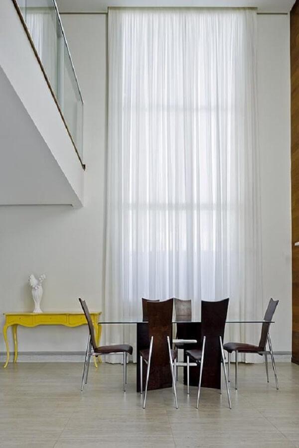 O aparador amarelo retrô se destaca na decoração do ambiente