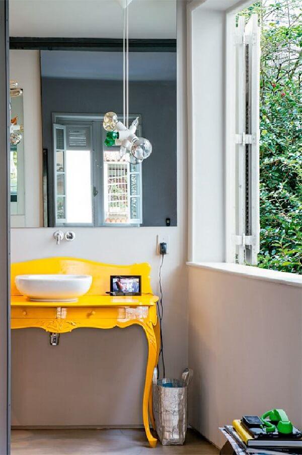 O aparador amarelo se transforma em bancada para banheiro