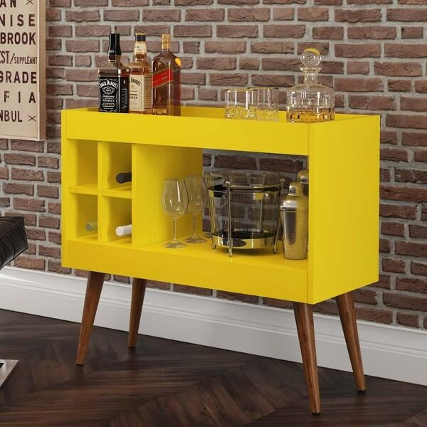 O aparador bar amarelo acomoda garrafas e taças