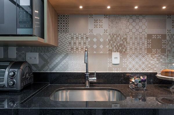 O azulejo antigo bege na cozinha quebra a sobriedade da bancada em granito preto