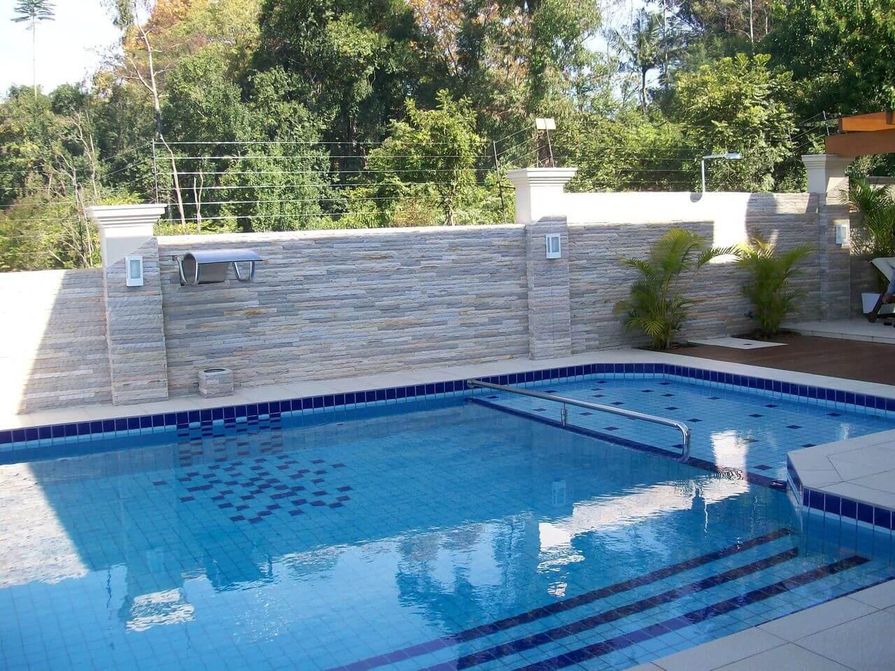 O azulejo para piscina em tons de azul foi usado em conjunto com o azulejo branco