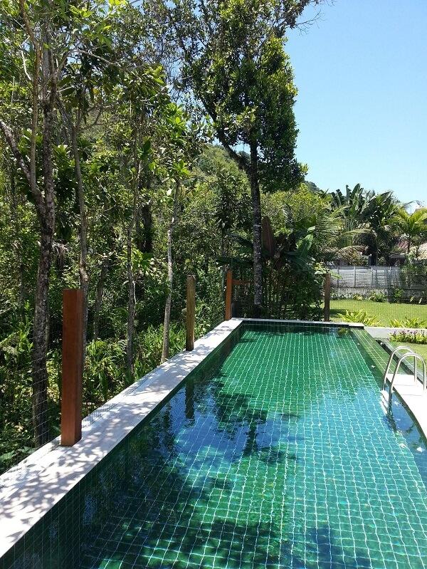 O azulejo para piscina verde conversa com a paisagem do local