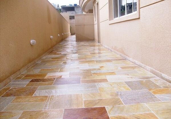 O revestimento de pedra São Tomé mesclado foi escolhido para compor o piso do corredor