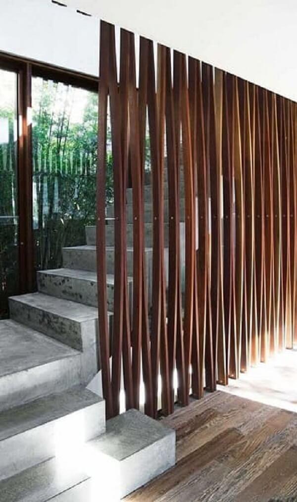 O revestimento para escada de concreto recebeu como guarda corpo o painel de madeira
