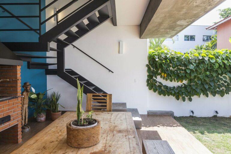 O revestimento para escada em ferro se conecta com a com churrasqueira tradicional em tijolos e demais elementos madeira