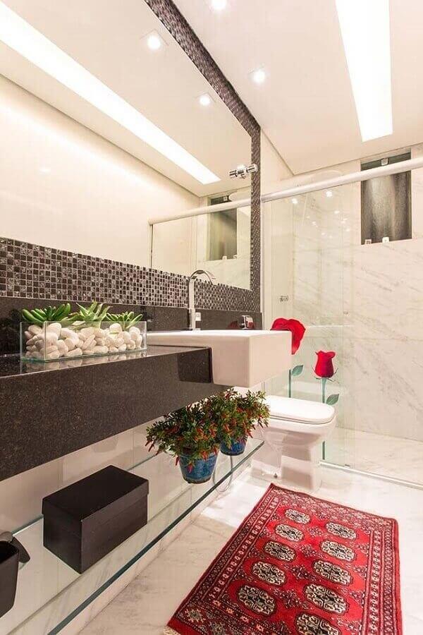 O revestimento pastilha preta serve como moldura do espalho do banheiro