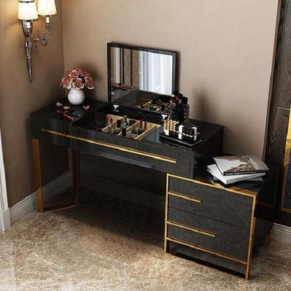 Os detalhes em dourado trazem requinte para a penteadeira preta