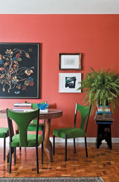 Parede cor coral e cadeiras verdes