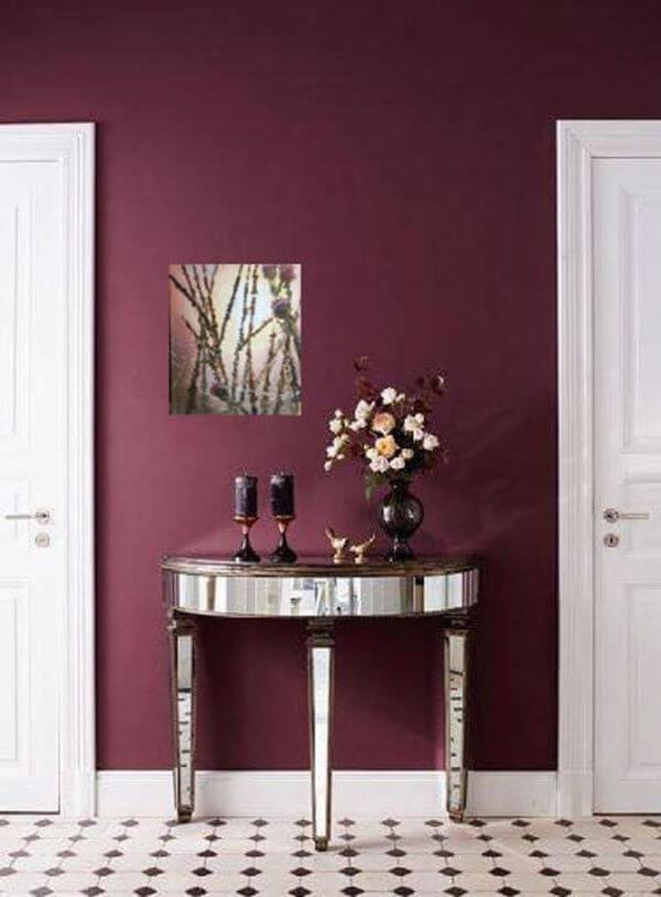 Parede cor vinho com mesa de apoio espelhada