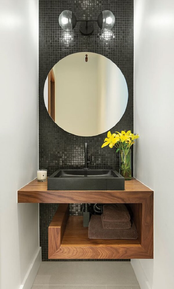 Parede estreita revestida com pastilha preta e espelho redondo