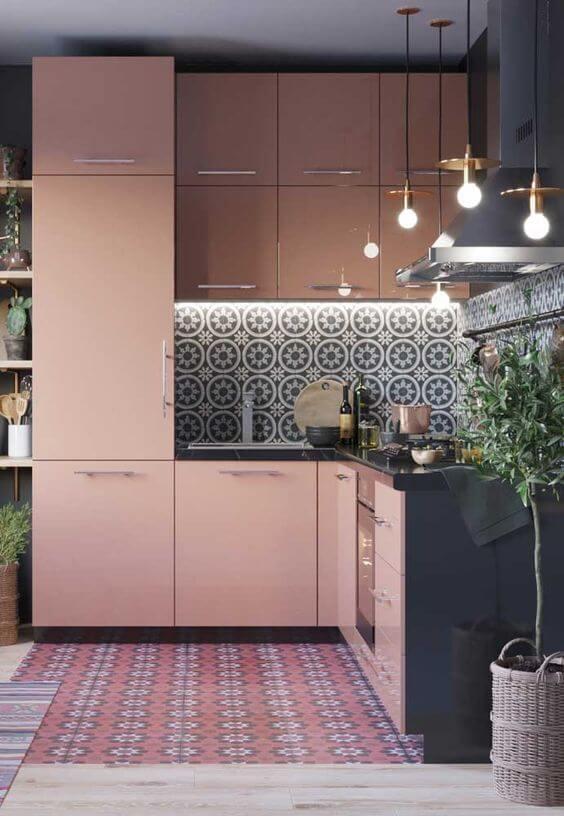 Pisos e azulejos antigos encantam a decoração dessa cozinha com móveis rosa