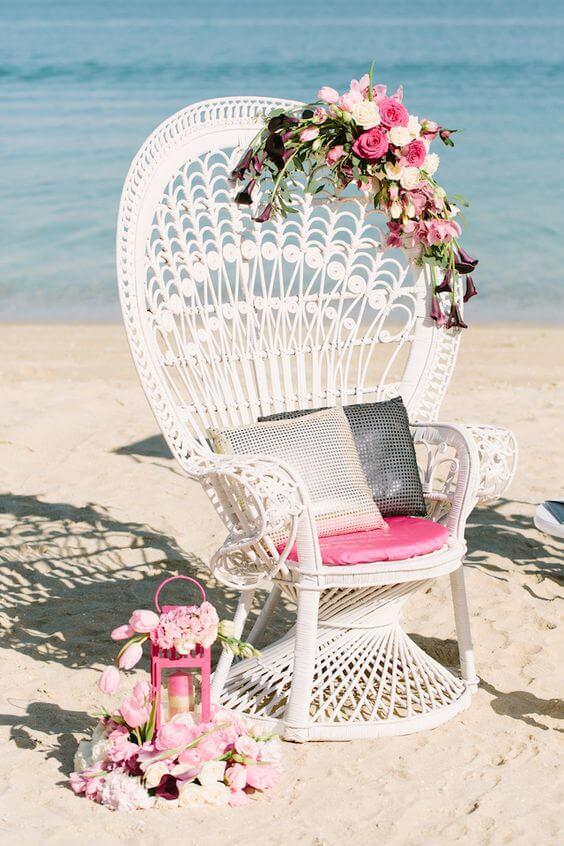 Poltrona de vime branca na praia decorada com flores cor de rosa