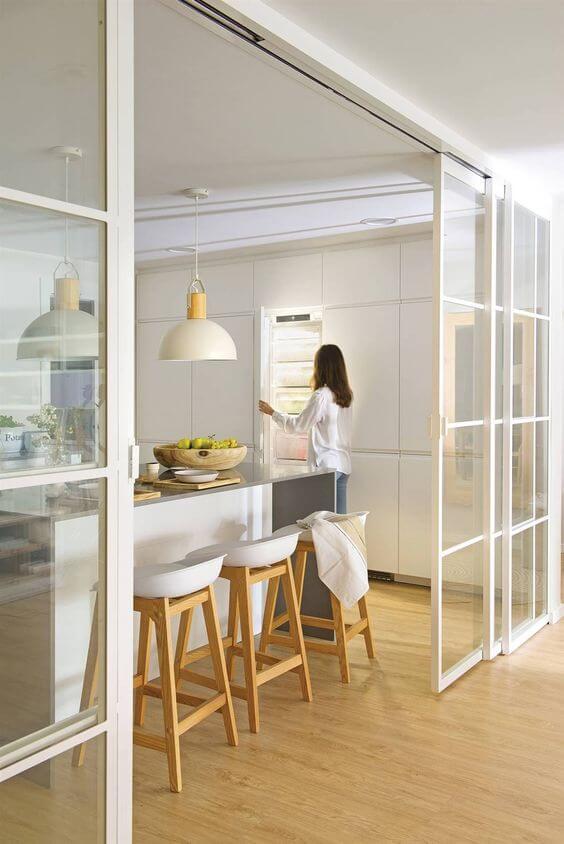 Porta branca com detalhes de vidro para dividir a cozinha da sala