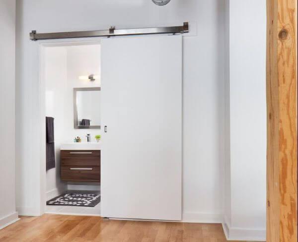 Porta branca de correr para banheiro no quarto moderno